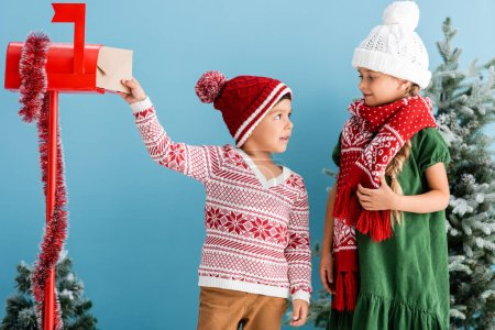 Photo for Boy in knitted sweater putting envelope in mailbox and looking at sister in winter outfit isolated on blue - Royalty Free Image