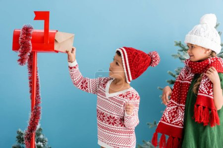 Photo for Boy in knitted sweater and hat putting envelope in mailbox near sister in winter outfit isolated on blue - Royalty Free Image