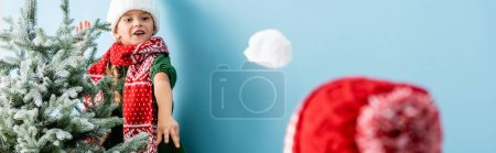 Photo for Panoramic crop of girl in scarf throwing snowball near brother in hat on blue - Royalty Free Image