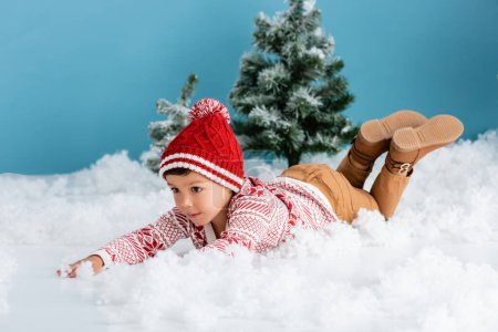 boy in winter outfit lying on white snow near christmas trees on blue