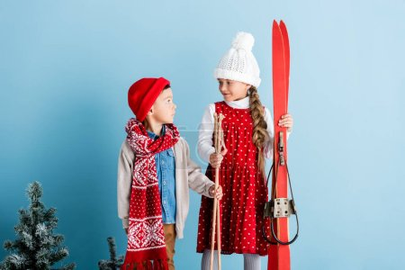 Photo for Girl in hat looking at boy while holding ski poles and skis on blue - Royalty Free Image