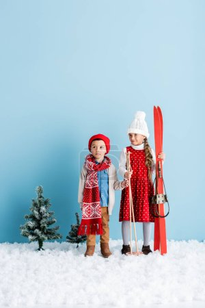 Photo for Girl holding ski poles and skis while standing on snow near brother in winter outfit on blue - Royalty Free Image