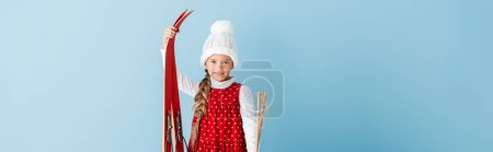 horizontal image of kid in winter outfit standing with ski poles and skis isolated on blue