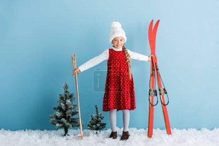 Photo for Child in winter outfit standing on snow with ski poles and skis on blue - Royalty Free Image