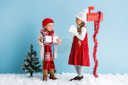 boy in winter outfit holding present near sister and mailbox on blue