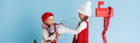 panoramic concept of boy in winter outfit holding present near sister and mailbox isolated on blue