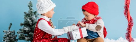 Photo pour Panoramic image of boy and girl in winter outfit sitting and touching present isolated on blue - image libre de droit