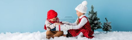 Photo for Panoramic shot of sister and brother in winter outfit sitting on snow and touching present on blue - Royalty Free Image