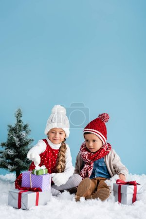 children in winter outfit sitting on snow and looking at presents near fir isolated on blue