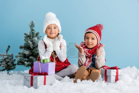 children in winter outfit sitting on snow and gesturing near presents and fir isolated on blue