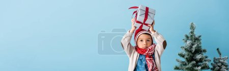 Photo pour Panoramic shot of boy in hat and winter outfit holding present above head near christmas trees isolated on blue - image libre de droit