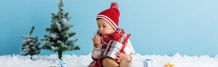 Photo pour Panoramic concept of boy in hat and winter outfit sitting on snow and holding present while blowing on hand isolated on blue - image libre de droit