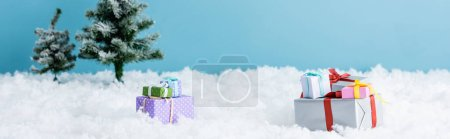 Photo pour Horizontal image of presents on white snow near christmas trees isolated on blue - image libre de droit