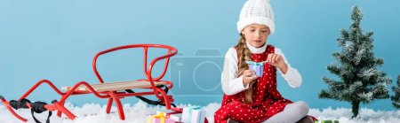 Photo pour Panoramic shot of kid in hat and winter outfit sitting on snow and holding present near sleigh isolated on blue - image libre de droit