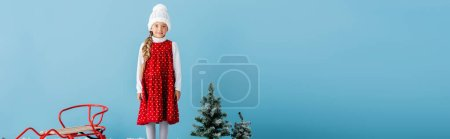 Photo pour Panoramic crop of girl in hat and winter outfit standing on near sleigh and pines isolated on blue - image libre de droit