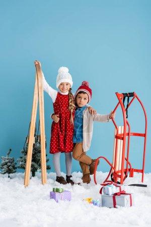 Photo pour Fille en tenue d'hiver tenant des skis et étreignant frère debout près de la traîne et des cadeaux sur la neige isolé sur bleu - image libre de droit