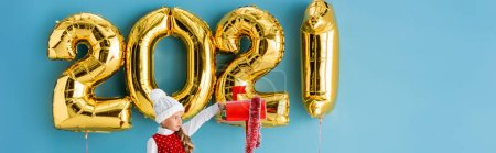 panoramic shot of girl in hat taking present from mailbox near balloons on blue