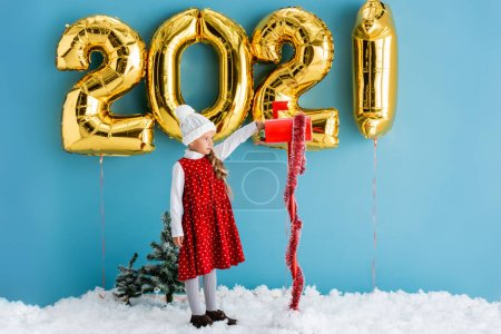 girl in hat taking present from mailbox near balloons with numbers while standing on snow on blue