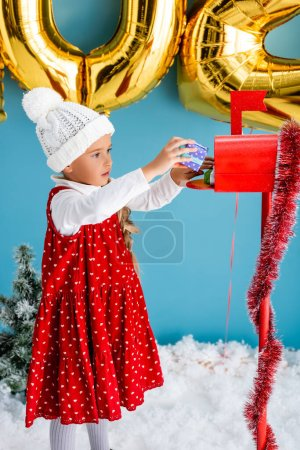 girl in hat and dress taking present from red mailbox on blue