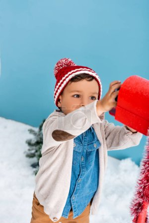 Photo for Boy in winter outfit reaching red mailbox on blue - Royalty Free Image