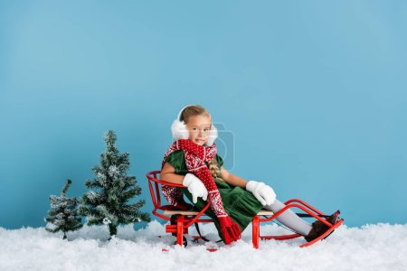 girl in winter earmuffs and scarf sitting in sleigh on snow near pines on blue