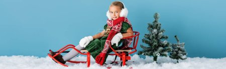 Photo pour Panoramic shot of girl in winter earmuffs and scarf sitting in sleigh on snow near pines on blue - image libre de droit