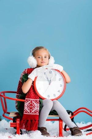 Photo pour Fille en hiver cache-oreilles et écharpe assis dans le traîneau et tenant horloge sur bleu - image libre de droit