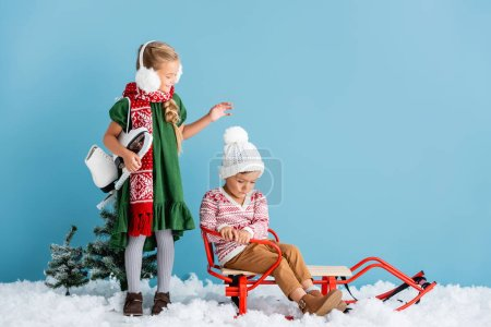 Photo for Girl in winter earmuffs and scarf standing with ice skates and looking at boy in sleigh on blue - Royalty Free Image