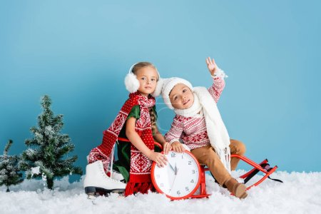 kids in winter outfit sitting on sleigh near clock, pines and ice skates on blue