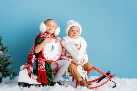 Photo pour Kids in winter outfit and scarfs sitting on sleigh near clock, pine and ice skates on blue - image libre de droit