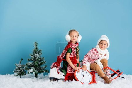 kids in scarfs and winter outfit sitting on sleigh near clock, pines and ice skates on blue