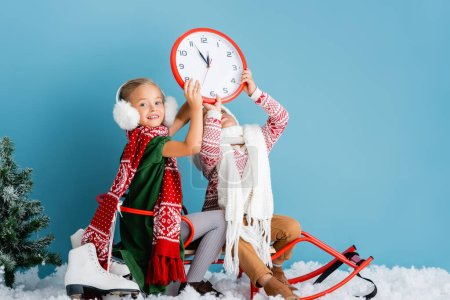 kids in winter outfit sitting on sleigh and holding clock near pine and ice skates on blue