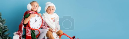 Photo pour Horizontal crop of kids in winter outfit and scarfs sitting on sleigh with clock near pine on blue - image libre de droit
