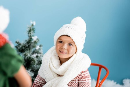 Photo for Selective focus of boy in knitted scarf and hat on blue - Royalty Free Image