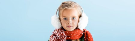Photo pour Panoramic crop of kid in winter earmuffs and scarf looking at camera isolated on blue - image libre de droit