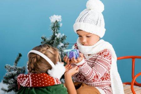 Photo pour Foyer sélectif du garçon en bonnet tricoté tenant présent tout en étant assis sur tour près de la fille en hiver cache-oreilles sur bleu - image libre de droit