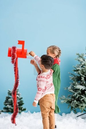 kids reaching envelope in red mailbox with decoration near pines on blue