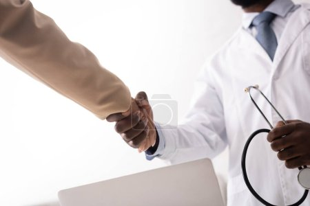 Photo for Selective focus of african american doctor holding stethoscope and shaking hands with patient - Royalty Free Image