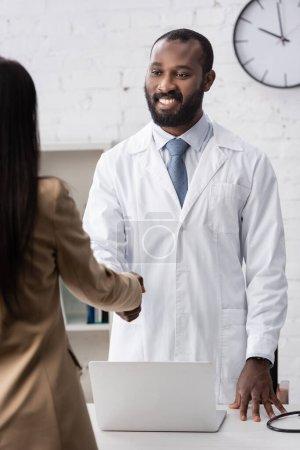 Photo pour Concentration sélective du médecin afro-américain debout et regardant le patient - image libre de droit