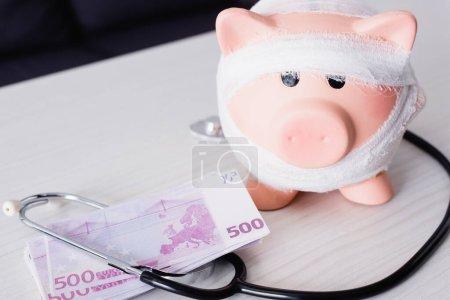Foto de Enfoque selectivo de alcancía cerca de estetoscopio y dinero en la mesa - Imagen libre de derechos