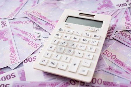 Photo pour Mise au point sélective du calculateur blanc sur les billets en euros - image libre de droit