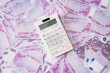 Photo pour Vue du dessus de la calculatrice blanche sur les billets en euros - image libre de droit