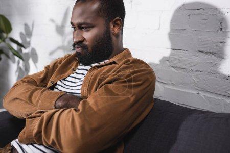 Photo pour Foyer sélectif de l'homme afro-américain assis sur le canapé avec les bras croisés - image libre de droit