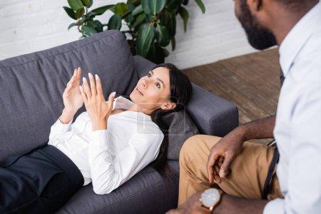 Photo pour Foyer sélectif de la femme couchée sur le canapé, parler et gestualiser psychologue afro-américain proche - image libre de droit
