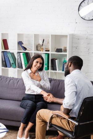 Photo pour Femme reconnaissante toucher la poitrine et serrer la main avec un psychologue afro-américain - image libre de droit