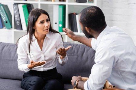 Photo pour Foyer sélectif du psychologue afro-américain apaisant patient frustré parler et gesticuler tout en étant assis sur le canapé - image libre de droit