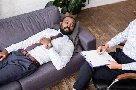 vue grand angle de l'homme afro-américain en tenue formelle couché sur canapé près psychologue écriture sur presse-papiers