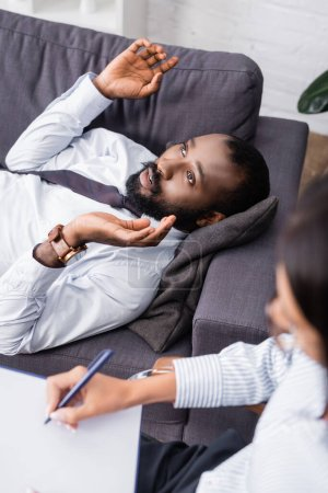 Photo pour Foyer sélectif de psychologue écrivant sur presse-papiers près d'un patient afro-américain parlant et gesticulant tout en étant couché sur le canapé - image libre de droit
