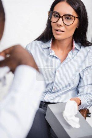 Photo pour Foyer sélectif de psychologue brune dans les lunettes tenant des serviettes en papier près du patient afro-américain stressé - image libre de droit
