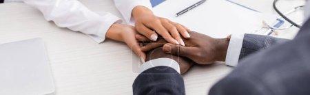 Photo pour Vue partielle du médecin touchant les mains d'un homme afro-américain près du presse-papiers et du stylo sur le bureau, image horizontale - image libre de droit